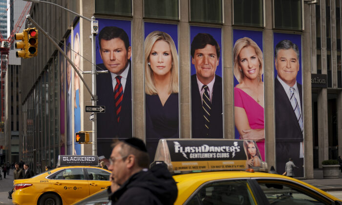 An advertisement features Fox News personalities, including Tucker Carlson and Sean Hannity, in New York City, on March 13, 2019. (Drew Angerer/Getty Images)