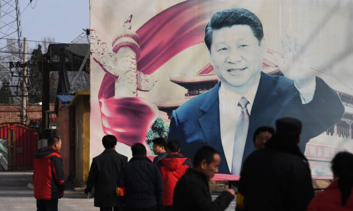 People stand near a faded propaganda billboard featuring an image of Chinese leader Xi Jinping, in a car park in Beijing on March 19, 2018. (Greg Baker/AFP via Getty Images)
