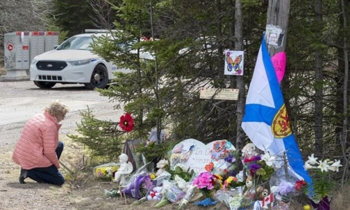 A woman pays her respects to victims of a mass shooting at a roadblock in Portapique, N.S. on April 22, 2020. (The Canadian Press/Andrew Vaughan)