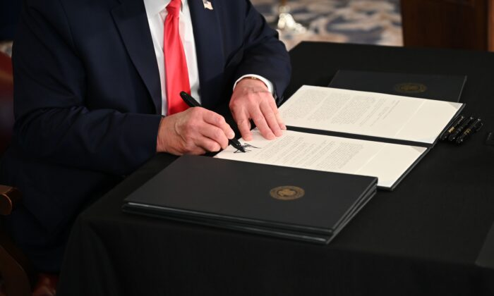 President Donald Trump signs an executive order in a file photo taken in Bedminster, N.J., on Aug. 8, 2020. (Jim Watson/AFP via Getty Images)