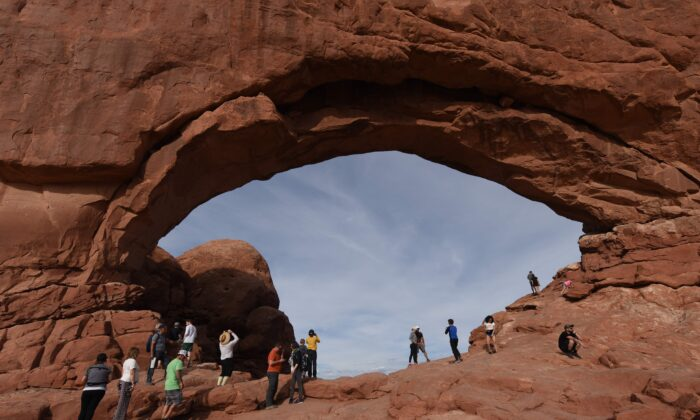 Tourists beside the North Window Arch at sunset in the Arches National Park near Moab, Utah on April 22, 2018. The park has over 2000 arches that were formed over 100 million years by a combination of water, ice, extreme temperatures and underground salt movement.  (Mark Ralston/AFP via Getty Images)