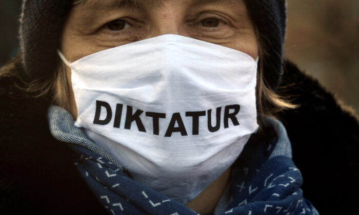 A woman wearing a protective face mask reading ''dictatorship'' protests against government restrictions, although the rally has been disallowed by a regional court, amid the CCP virus disease (COVID-19) outbreak, in Bremen, Germany, on Dec. 5, 2020. (Fabian Bimmer/Reuters)