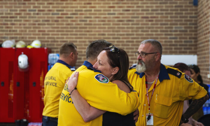 Melissa O'Dwyer, whose husband Andrew O'Dwyer was killed while on duty as a volunteer firefighter, is hugged by a member of the Horsley Park Rural Fire Brigade  in Sydney, Australia on Dec. 22, 2019. (Jenny Evans/Getty Images)