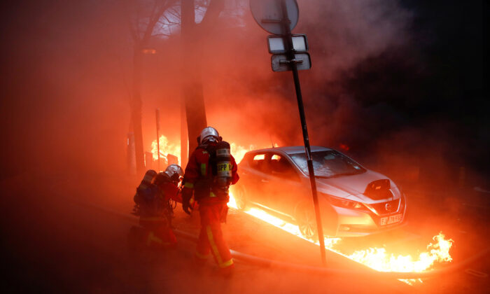 "Firefighters work next to a car surrounded by flames during a protest against the ""Global Security Bill""  in Paris on Dec. 5, 2020. (Gonzalo Fuentes/Reuters)"