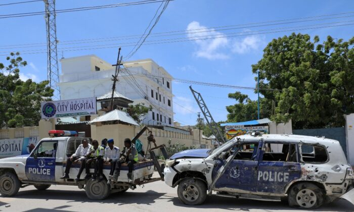 Somali police officers tow their car from the scene of a roadside explosion in Hodan district of Mogadishu, Somalia, on July 8, 2020. (Feisal Omar/File Photo, Reuters)