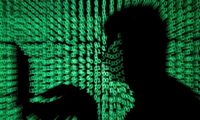 Een man houdt een laptop vast terwijl cybercode op hem wordt geprojecteerd in deze illustratiefoto gemaakt op 13 mei 2017. (Kacper Pempel / Reuters)