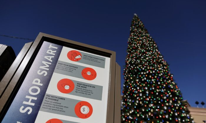 A coronavirus advisory sign is seen in front of a Christmas tree at the Citadel Outlet mall, in Commerce, Calif., on Dec. 3, 2020. (Lucy Nicholson/Reuters)
