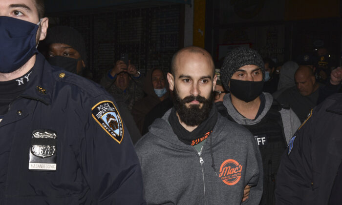 Mac's Public House co-owner Danny Presti is taken away in handcuffs after being arrested by New York City sheriff's deputies in the Staten Island borough of New York, Tuesday, Dec. 1, 2020.  (Steve White via AP)