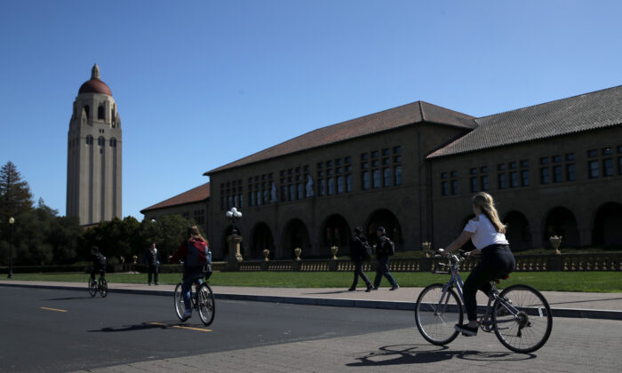 Cyclists ride by Hoover Tower on the Stanford University campus in Stanford, Calif., on March 12, 2019. (Justin Sullivan/Getty Images)