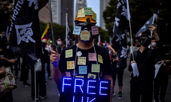 """An activist dresses as a human """"Lennon Wall"""" before an anti-China protest to mark the 71st anniversary of the founding of the People's Republic of China in Shinjuku district of Tokyo on October 3, 2020. (Philip Fong/AFP via Getty Images)"""