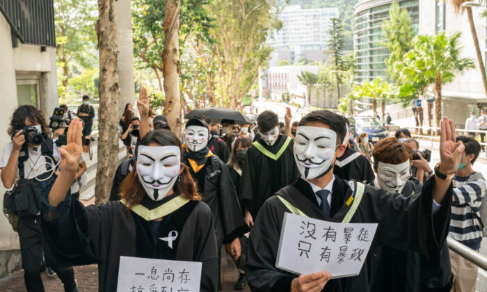Students wearing black graduation gowns and Guy Fawkes masks march at the Chinese University of Hong Kong campus in Hong Kong on Nov. 19, 2020. (Anthony Kwan/Getty Images)