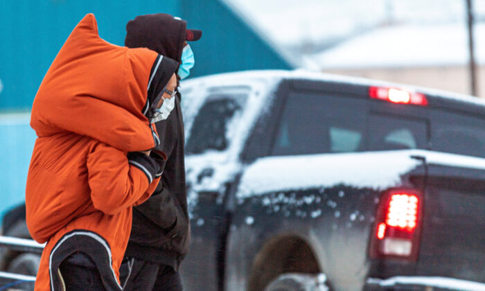 People wear masks while they walk as the territory of Nunavut enters a two week mandatory restriction period in Iqaluit, Nunavut, Canada, on Nov. 18, 2020.  (Natalie Maerzluft/Reuters)