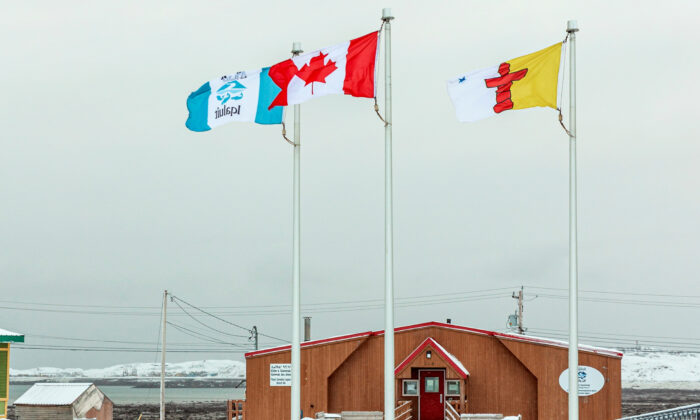 Flags of Iqaluit, Canada and the territory of Nunavut fly over the Elders' Qammaq, a drop-in centre, as Nunavut enters a two week mandatory coronavirus disease (COVID-19) restriction period in Iqaluit, Nunavut, Canada November 18, 2020.  (Reuters/Natalie Maerzluft/File Photo)