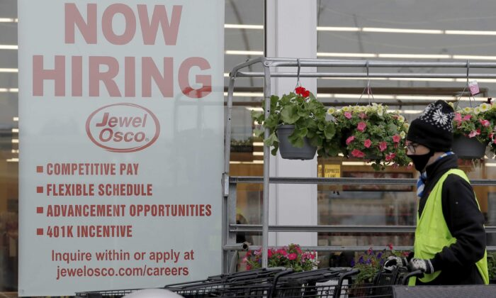 A man pushes carts as a hiring sign shows at a Jewel Osco grocery store in Deerfield, Ill., on April 23, 2020. (Nam Y. Huh/AP Photo)
