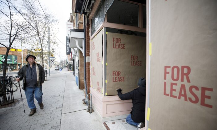 """A worker posts fake """"for lease"""" signage on a storefront in the Roncesvalles neighbourhood of Toronto as part of a protest against the Ontario government's pandemic lockdown rules, on Nov. 24, 2020. (The Canadian Press/Cole Burston)"""