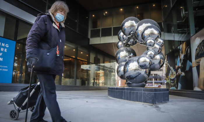 A woman wearing a mask walks past a sculpture in Calgary, Alta., on Dec. 2, 2020. (Jeff McIntosh/The Canadian Press)