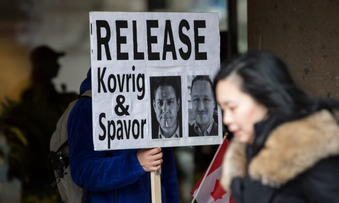 A young man holds a sign bearing photographs of Michael Kovrig and Michael Spavor, who have been detained in China for more than a year, outside B.C. Supreme Court where Huawei chief financial officer Meng Wanzhou was attending a hearing, in Vancouver, Canada, on Jan. 21, 2020. (Darryl Dyck/The Canadian Press)