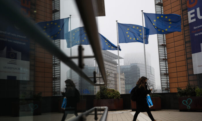 A pedestrian walks past the European Commission headquarters in Brussels, Monday on Dec. 7, 2020. (Francisco Seco/AP)
