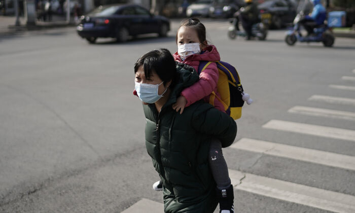 People wearing protective face masks walk along a business street in Wuhan, China, on Dec. 5, 2020. (Getty Images)