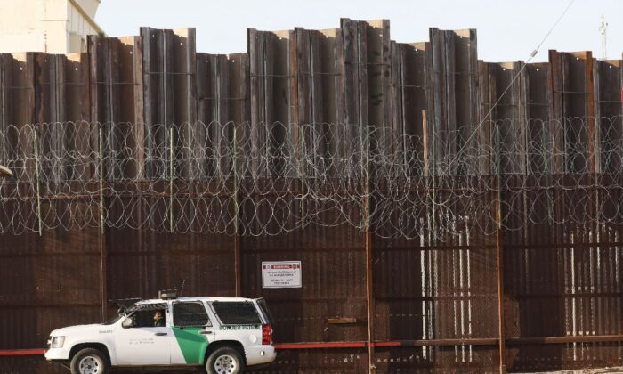 A Border Patrol agent is posted in front of the U.S.-Mexico border barrier in Imperial County, which has been hard-hit by the COVID-19 pandemic in Calexico, Calif. on July 24, 2020. (Mario Tama/Getty Images)