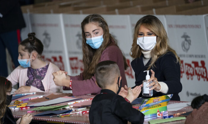 First Lady Melania Trump offers hand sanitizer to a child as they make Christmas cards during the annual Marine Toys for Tots Drive at Joint Base Anacostia-Bolling in Washington on Dec. 8, 2020. (Drew Angerer/Getty Images)
