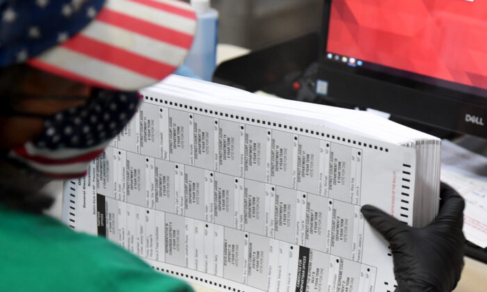 An election worker is seen in a file photo scanning mail-in ballots. (Ethan Miller/Getty Images)