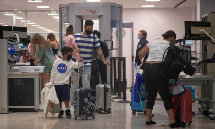 A family wears face masks as they pass security at Terminal A of IAH George Bush Intercontinental Airport amid the coronavirus disease (COVID-19) outbreak in Houston, Texas, on July 21, 2020. (Adrees Latif/Reuters)