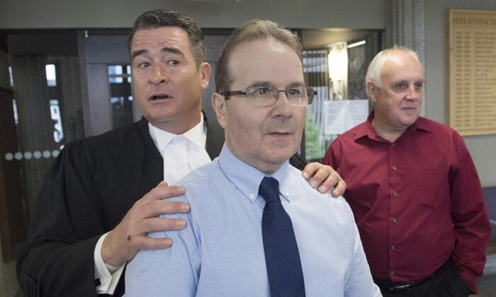 Glen Assoun, the Nova Scotia man who spent almost 17 years in prison for a crime he didn't commit, his lawyer Sean MacDonald and Ron Dalton, right, from the advocacy group Innocence Canada, stand outside Supreme Court in Halifax on July 12, 2019. (The Canadian Press/Andrew Vaughan)