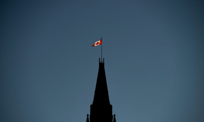 The Canadian Flag is illuminated by morning light atop the Peace Tower on Parliament Hill in Ottawa on Sept. 17, 2018. (Sean Kilpatrick/The Canadian Press)