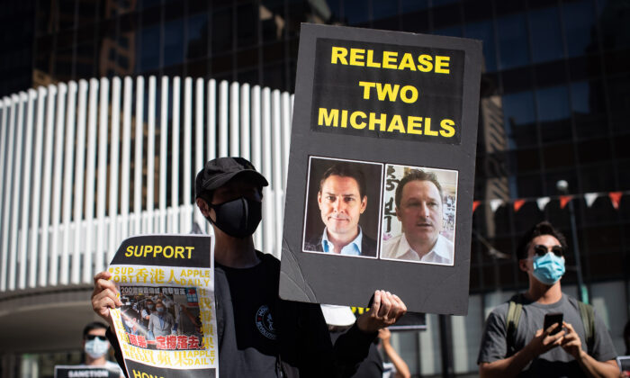 A person holds a sign with photographs of Michael Kovrig and Michael Spavor, who have been detained in China since Dec. 10, 2018, as people gather for a rally in support of Hong Kong democracy, in Vancouver on Aug. 16, 2020. (The Canadian Press/Darryl Dyck)