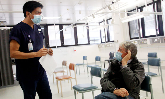 Registered Nurse Laxman Adhikari speaks with John Eberhardt in the clinical assessment room at St George Hospital in Sydney, Australia on May 15, 2020. (Maree Williams/Getty Images)