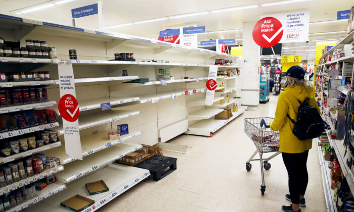 A lone shopper looks at empty shelves in a supermarket in Manchester, England, on March 18, 2020. (Clive Brunskill/Getty Images)