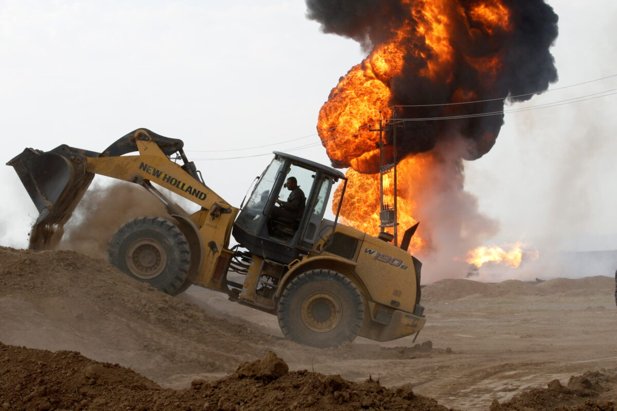A machinery is seen as oil wells burn