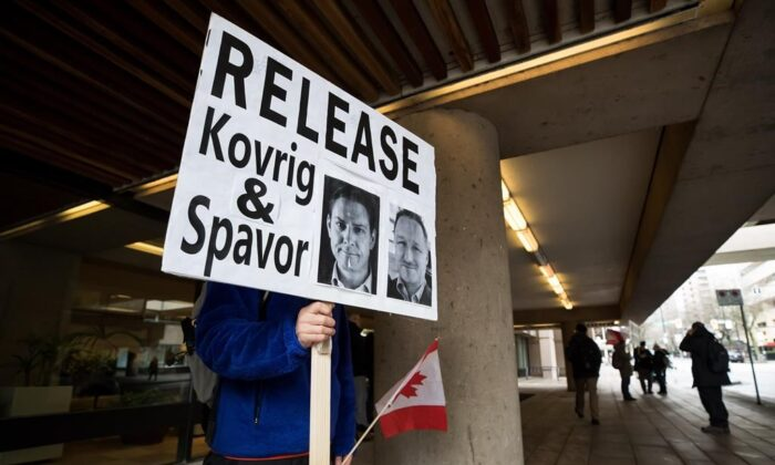 A young man holds a sign bearing photographs of Michael Kovrig and Michael Spavor, who have been detained in China for two years, outside B.C. Supreme Court during a hearing for  Huawei chief financial officer Meng Wanzhou on Jan. 21, 2020. (The Canadian Press/Darryl Dyck)
