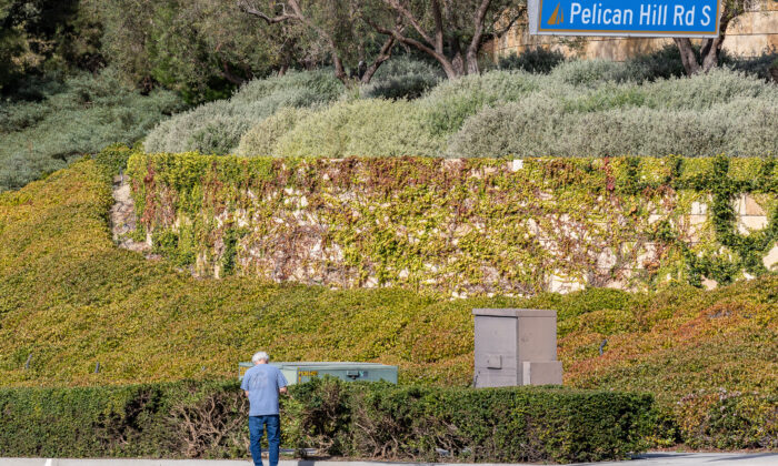 A man pays respects near the site of a crash that killed two parents and injured their three children in Newport Beach, Calif., on Dec. 9, 2020. (John Fredricks/The Epoch Times)