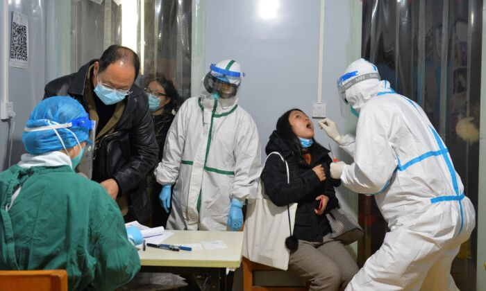 Health workers are conducting nucleic acid tests on residents of Chengdu, China, on Dec. 8, 2020. (STR/AFP via Getty Images)