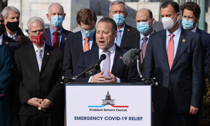 Rep. Josh Gottheimer (D-NJ) (C) and Rep. Tom Reed (R-NY) (3rd R), co-chairs of the bipartisan Problem Solvers Caucus, hold a news conference with fellow members of Congress to highlight the need for bipartisan, bicameral COVID-19 relief legislation outside the U.S. Capitol in Washington on Dec. 3, 2020. (Chip Somodevilla/Getty Images)