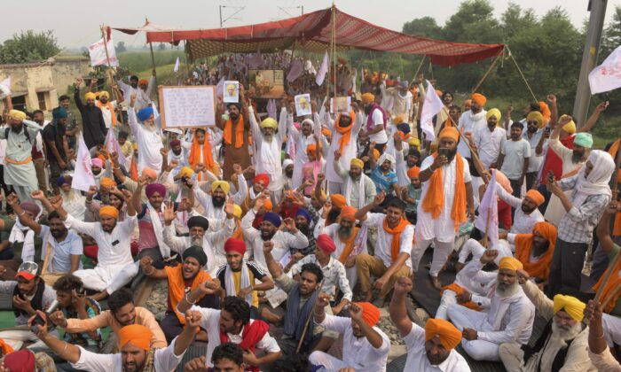 Farmers shout slogans while blocking railway tracks, on the outskirts of Amritsar, during a protest against Indian Prime Minister Narendra Modi's government following the recent passing of new farm bills in parliament, on Sept. 28, 2020. (Narinder Nanu/AFP via Getty Images)