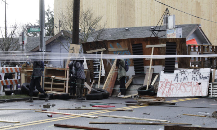 Protesters stand behind barricades at their encampment outside a home in Portland, Ore., on Dec. 9, 2020. (AP Photo/Gillian Flaccus)