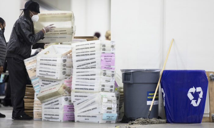 A worker with the Detroit Department of Elections helps stack empty boxes used to organize absentee ballots after nearing the end of the absentee ballot count at the Central Counting Board in the TCF Center in Detroit, Mich. on Nov. 4, 2020. (Elaine Cromie/Getty Images)