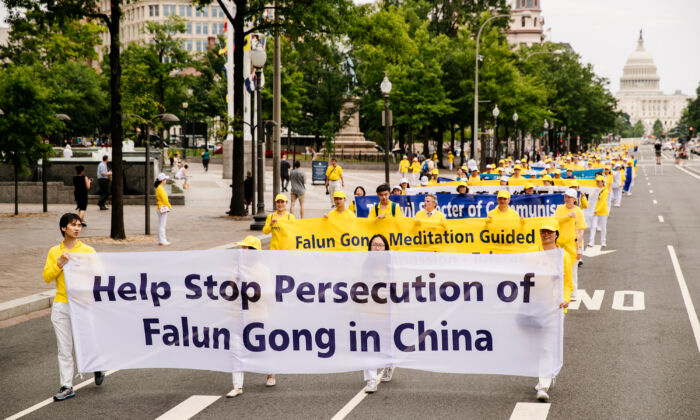 Local Falun Gong practitioners take part in a grand march calling for an end to the persecution of the spiritual practice in China, in Washington on June 20, 2018. (Edward Dye/The Epoch Times)