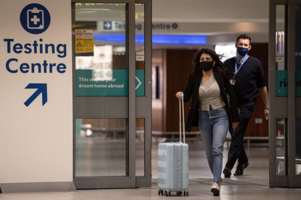 A passenger walks past a sign directing people to a novel coronavirus Covid-19 testing site adjacent to Terminal 1 of Manchester Airport in Manchester, northern England on December 3, 2020.