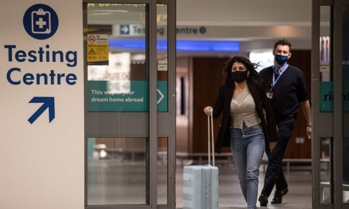 A passenger walks past a sign directing people to a CCP virus testing site adjacent to Terminal 1 of Manchester Airport in Manchester, northern England, on Dec. 3, 2020. (Oli Scarff/AFP via Getty Images)