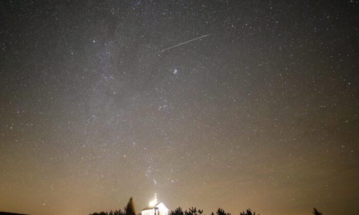 A meteor streaks across the sky during the annual Geminids meteor shower over an Orthodox church on the local cemetery near the village of Zagorie, some 69 miles west of capital Minsk, Belarus, on Dec. 13, 2017. (Sergei Grits/AP Photo)
