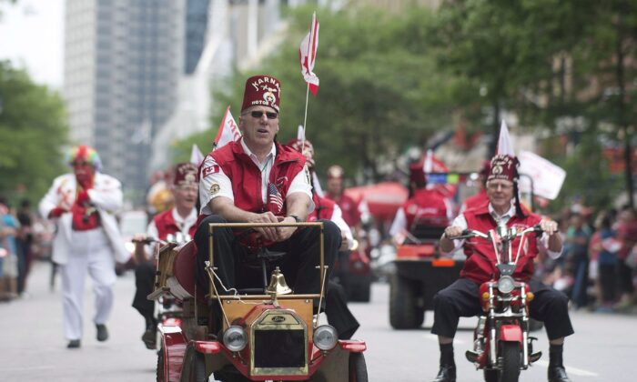 Members of the Shriners entertain the crowd as they participate in the annual Canada Day parade in Montreal. (The Canadian Press/Graham Hughes)