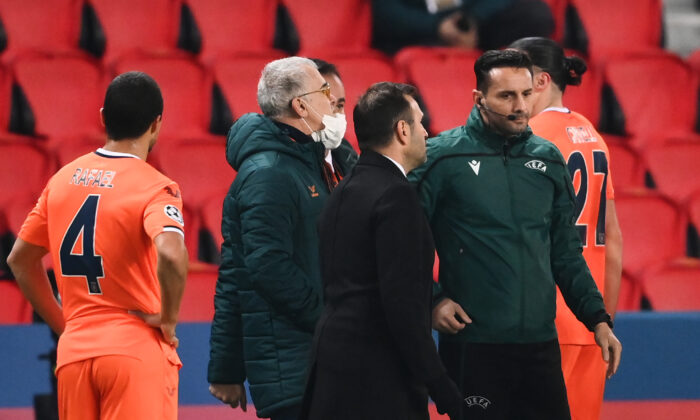 Istanbul Basaksehir's Turkish coach Okan Buruk (2ndR) talks to Romanian 4th referee Sebastian Coltescu (R) after the game was suspended in the first half as the players walked off amid allegations of racism by one of the match officials during the UEFA Champions League group H football match between Paris Saint-Germain (PSG) and Istanbul Basaksehir FK at the Parc des Princes stadium in Paris, on Dec. 8, 2020. 