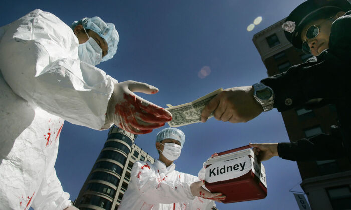 Falun Gong practitioners demonstrate an illegal act of paying for human organs, which happens in China, in Washington, D.C., on April 19, 2016. (JIM WATSON/AFP via Getty Images)