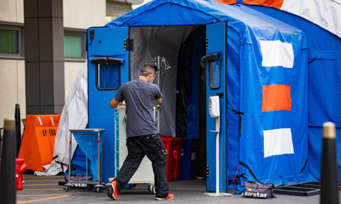 A hospital worker walks equipment into an emergency triage tent set up outside of Kaiser Permanente's Orange County Medical Center in Irvine, Calif., on Dec. 11, 2020. (John Fredricks/The Epoch Times)