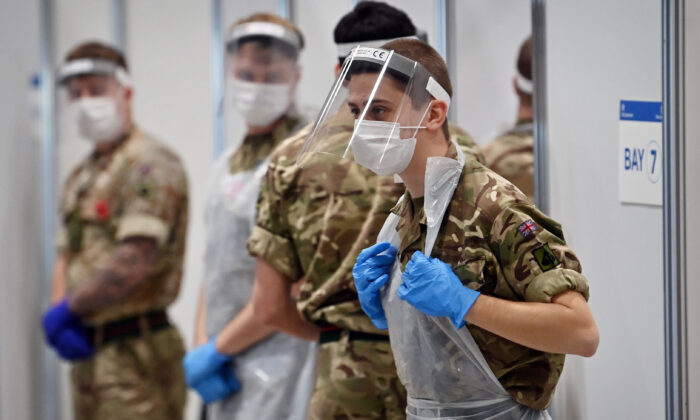 Soldiers wearing full PPE in the form of face shields, gloves, face masks and bibs wait to assist CCP virus testing at a rapid testing centre in the Liverpool exhibition centre in Liverpool, England, on Nov. 11, 2020 (Paul Ellis/AFP via Getty Images)