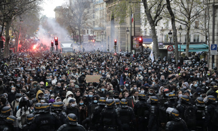 Demonstrators are blocked by police officers during a protest against a proposed bill in Paris, France, on Dec. 12, 2020. (Lewis Joly/AP Photo)